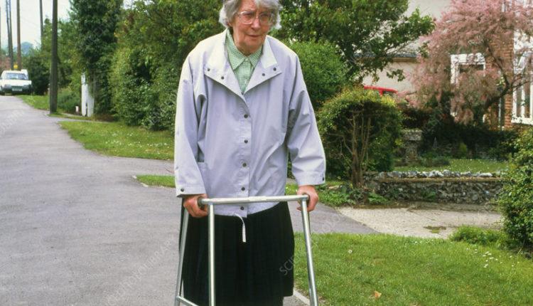 Old woman walks along street using walking frame